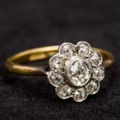An 18 ct gold and diamond flowerhead set ring The central stone spreading to approximately 0.