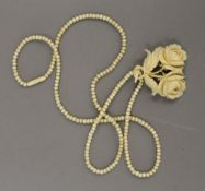 A Victorian ivory bead necklace with carved ivory floral pendant