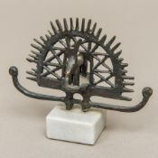 A Turkish cast bronze archaistic group, worked as a stylised stag within a pierced arch,