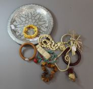 A white metal dish and a quantity of amber,