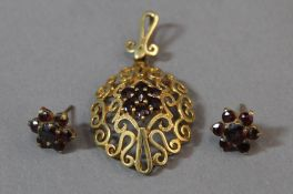An unmarked gold and garnet pendant, together with a pair of ear studs (6.