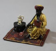 A cold painted bronze model of an Arab smoking a pipe