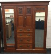 An Edwardian walnut compactum wardrobe, typically fitted and carved with fruiting panels.