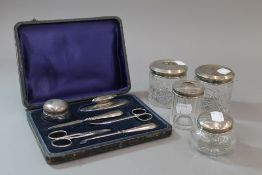 Four silver topped glass dressing table jars,