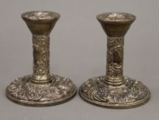 A pair of embossed silver candlesticks (11 troy ounces loaded)