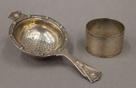 A silver napkin ring and a silver tea strainer (2.