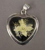 A silver flower form pendant