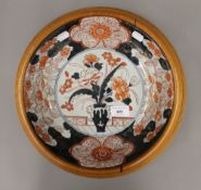 A 19th century Japanese Imari dish in an oak frame
