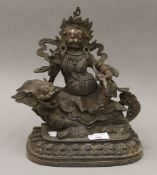A bronze figure of a deity seated on a dog-of-fo