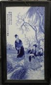 A large Chinese blue and white porcelain plaque, depicting figures before a river with calligraphy,