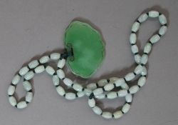 A celadon jade necklace and pendant