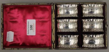 A cased set of six silver napkin rings,