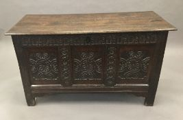 A 17th/18th century carved oak three panelled coffer.