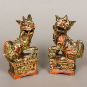 A pair of Chinese antique polychrome and gilt decorated pottery temple lion incense stick holders,