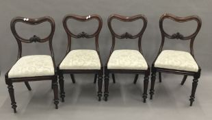 A set of four 19th century mahogany balloon back dining chairs with carved rail and drop-in seat