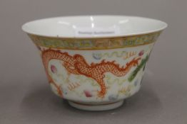 A Chinese porcelain bowl, decorated with a dragon and a phoenix chasing a flaming pearl,