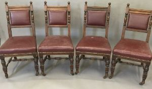 A set of four late Victorian leather upholstered walnut dining chairs