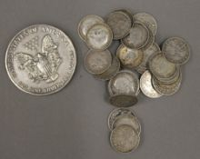 A one ounce 1990 USA silver dollar and thirty-three silver three penny pieces