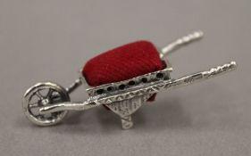A silver pin cushion formed as a wheelbarrow