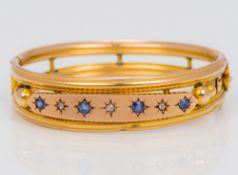 A 9 ct gold sapphire and diamond set bangle form bracelet Of pierced tubular form,