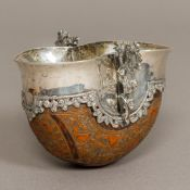 An 19th century white metal (probably silver) mounted carved coquilla nut twin handled tasting