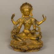 A gilt bronze model of a Tibetan four-armed deity Set with small coral and turquoise cabochons,