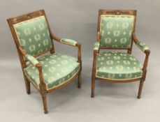 A pair of French Empire period walnut and beech framed upholstered open armchairs Each with laurel