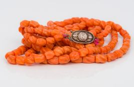 A Chinese carved coral bead three strand necklace Set with a silver clasp,