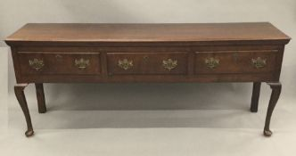 A George III oak low dresser The moulded rectangular top above three frieze drawers with brass