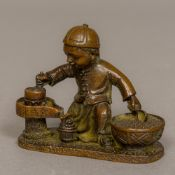 A Chinese bronze group worked as a young street vendor juicing fruit Incised mark. 6.5 cm high.