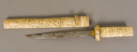 A 19th century Japanese carved bone tanto The handle and scabbard typically worked with figures in