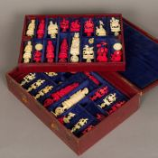 A late 19th/early 20th century carved and stained ivory chess set Each piece intricately carved,
