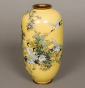 A Japanese cloisonne vase Decorated with cranes amongst floral sprays on a sand coloured ground,