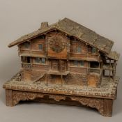 A late 19th century Black Forest carved wooden music box/clock Formed as an Alpine Chalet.