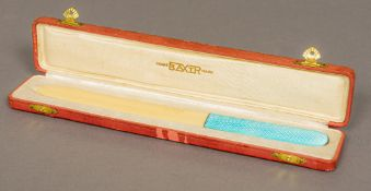 A white and enamel handled ivorine letter opener The handle engine turned, in fitted case.