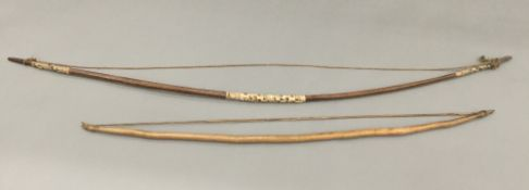 Two Fijian tribal bows Each of typical form. The largest 175 cm long.