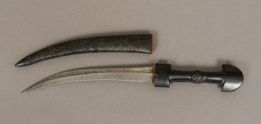 A 19th century Jambiya with leather sheath The steel blade typically curved, the handle carved.