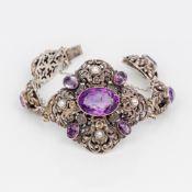 An amethyst and pearl set silver bracelet The links of pierced scrolling foliate form.