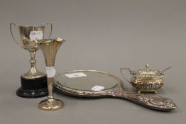 A silver mustard pot, a silver bud vase, a small silver trophy cup and a silver backed mirror (2.