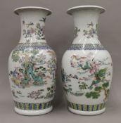 A pair of 20th century Chinese porcelain vases, hand painted with figures in a landscape,