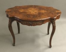 A Victorian serpentine shaped walnut centre table with carved frieze drawers