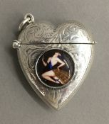 A silver heart shaped vesta decorated with an elegant lady