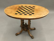 A Victorian walnut chessboard inlaid games table