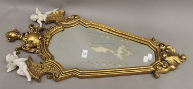A gilt decorated cherub mounted mirror