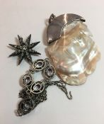 A white metal dress necklace together with a star brooch and a carved mother-of-pearl and 925