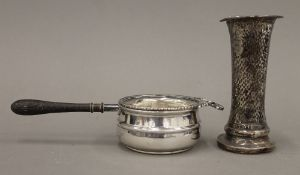 A silver tea strainer and a loaded beaten silver vase (6.