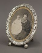 An antique sterling silver photograph frame on ball feet