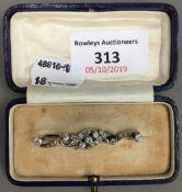 An unmarked gold diamond set bar brooch (5.