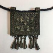 An Eastern white metal pendant