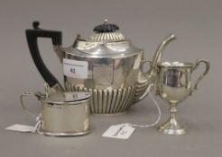 A small silver teapot, a silver mustard pot and a small silver trophy cup (9.